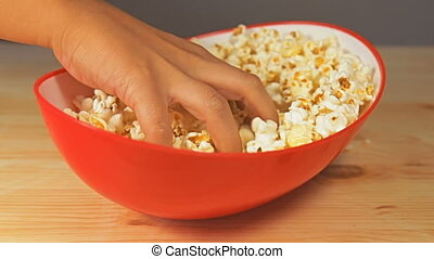 Close-up view of hand that tries to grab as many popcorn...