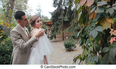 Close-up view of happy european wedding couple in nature. Groom in suit hugs the bride and straightens her wedding dress on his shoulder against the background of fir trees and a house in the forest.