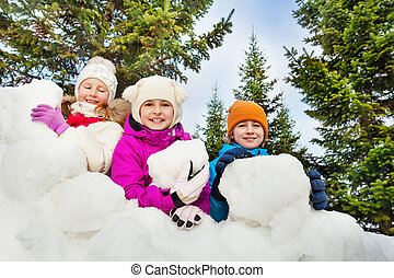 Close-up view of happy kids behind the snow fort