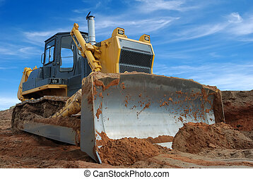 Close-up view of heavy bulldozer with blade standing in sandpit at low camera angle against bright blue sky