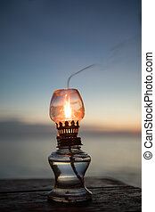 close up view of kerosene lamp on sunset beach back