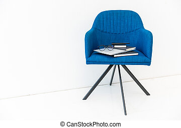 close up view of laptop, black notebooks and eyeglasses on blue chair on white backdrop