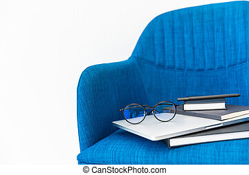 close up view of laptop, black notebooks and eyeglasses on blue chair on white background