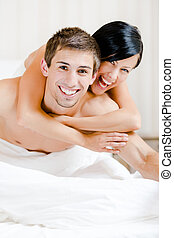 Close up view of laughing couple who plays in bed