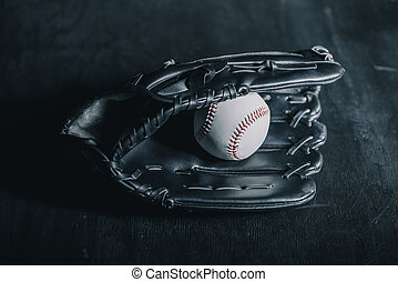Close-up view of leather baseball glove and ball on black