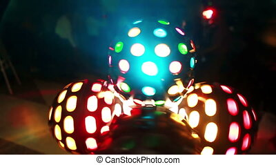 Close-up view of light ball. Colored disco projector rounding. Light show shining in the dark in night club.