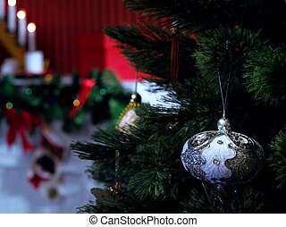 close up view of lit Christmas tree with toy and fireplace on the back