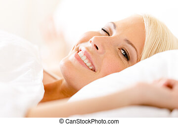 Close up view of lying in bed woman on white pillow