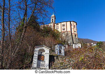 Close up view of Madonna del Sasso church above Locarno city on the stair way , a sanctuary and pilgrimage church in Orselina, in autumn on sunny day with blue sky in background, Ticino, Switzerland