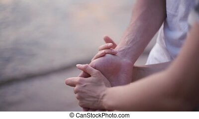 Close-up view of male and female hands. Young couple standing on the shore of the sea, on the beach, holding hands.