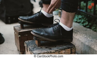 Close-up view of male feet on a stand. Shoe shiner working on the street, polishing the black shoes in downtown.