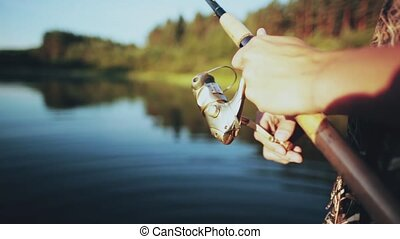 Close-up view of male hands holding the fishing rod. Young...