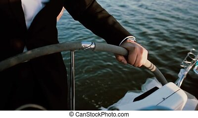 Close-up view of male hands standing behind steering wheel on the yacht. Young businessman resting with favorite hobby.