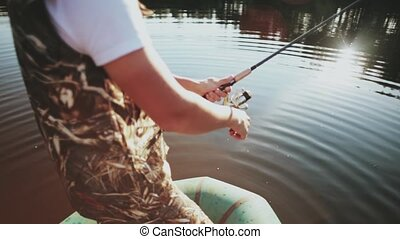 Close-up view of male hands uses the rod with spinning reel....