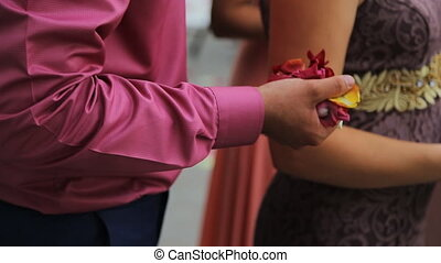 Close up view of man hand with handful of rose petals and rice.