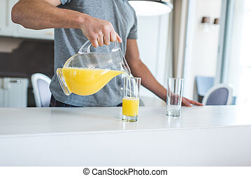 man pouring orange juice