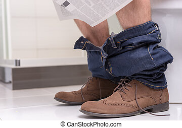 Close up view of man reading newspaper while sitting on the toilet seat