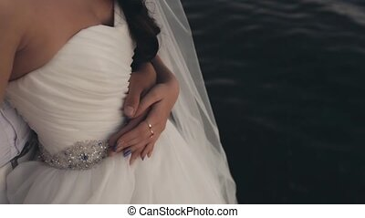Close-up view of man standing behind woman and hugging her. Bride and groom couple sailing on the yacht.