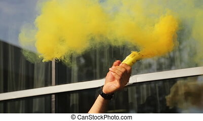 Close up view of man waving smoke float of saturated yellow...