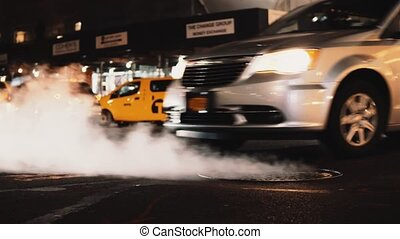 Close-up view of manhole cover with flying smoke, fume on the traffic road in downtown of New York, America.