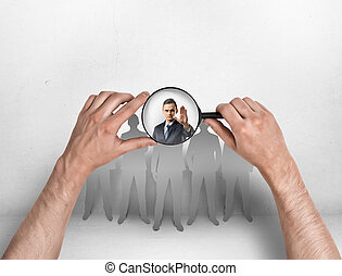 Close-up view of man's hands focusing magnifier on businessman with his hand raised