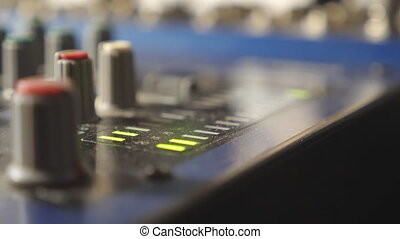 Close up view of mixer soundboard with knobs and flashing...