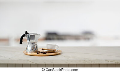 Close up view of mock pot and coffee cup on marble desk with blurred kitchen