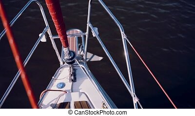 Close-up view of nasal part of the ship. Sailboat going through the blue water in sunny day. Yacht sailing in the winds.