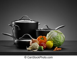 close up view of nice cookware set with some vegetables on grey back