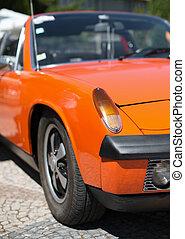Close-up view of orange retro car headlight.