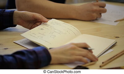 Close-up view of people writing and drawing important information.