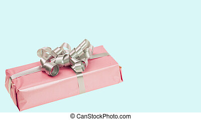 Close up view of pink present box isolated on blue background. Holidays concept.