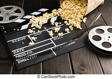 close up view of popcorn in paper container and movie clapper board on table, Movie time concept
