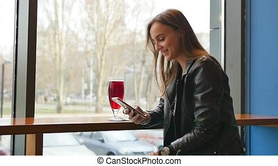 Close up view of pretty young businesswoman drinking coffee and sending messages with her mobile phone while being in a caf . Modern communication, surfing internet, social networks. Female portrait. Slow motion.