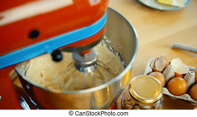 Close-up view of red mixer blending the dough, ingredients in big bowl. Confectioner cooking the desserts.