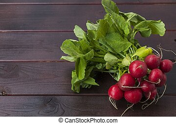 Close up view of red radish on brown wooden background isolated. Healthy food concept.