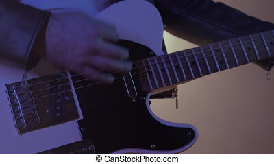 Close-up view of rock musician mans hands masterfully playing electric guitar. Fingers tapping strings in smoky spotlight during concert on stage