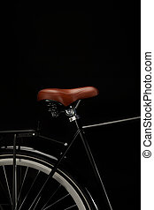 close-up view of saddle and wheel of vintage bicycle isolated on black