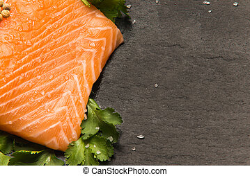 close up view of salmon fillet with coriander in black background with copy space for text
