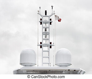Close up view of satellite domes on top of a super yacht over cloudy sky background