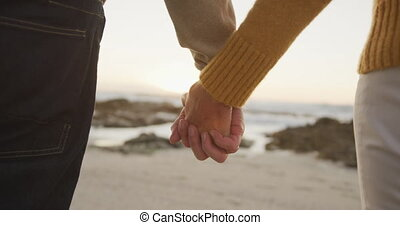 Close up view of senior couple holding hands at beach