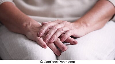 Close up view of senior woman folded wrinkled hands. Lonely elder lady sitting alone with clasped arms. Old people loneliness, geriatric diseases, elderly health care problems and social support concept