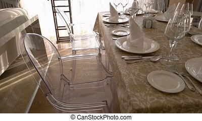 Close up view of served table and chairs in living room. Table setting with glasses, plates, cutlery and napkins.