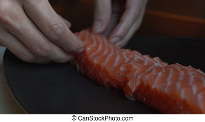 Close up view of serving salmon on the plate. Preparing salmon for presentation on the plate