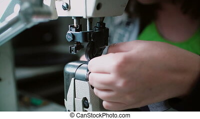 Close-up view of sewing machine for shoes. Woman s hand working at the factory with thread. 4K