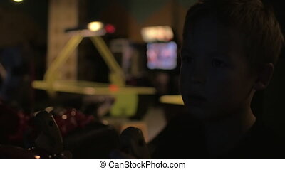 Close up view of small boy are playing video arcade game in...