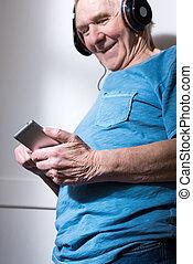Close-up view of smiling senior man in headphones using smartphone