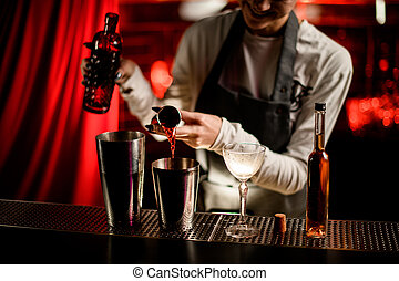 close-up view of steel shaker cup in which bartender pours drink from jigger