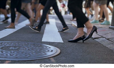 Close-up view of stylish female feet. Businesswoman crossing the road in crowded downtown. Slow motion.