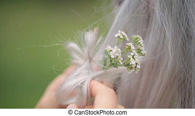 Close up view of stylist putting flowers in model hair.